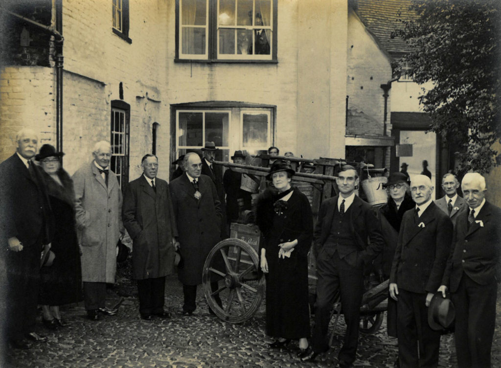 Image of the founders of the Museum of Cambridge. A black and white photograph of men and women gathered in the courtyard.