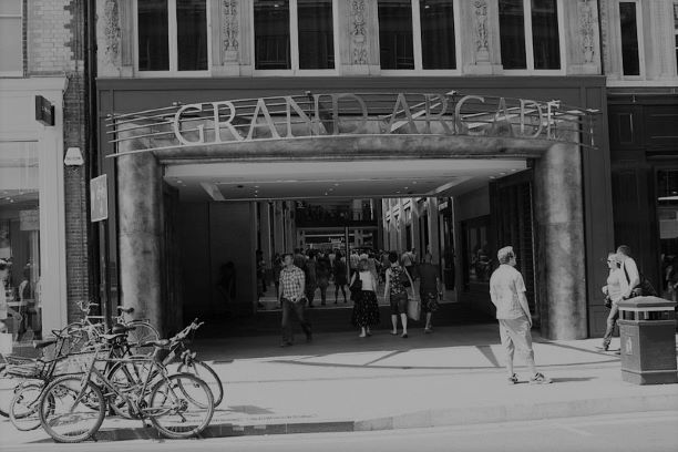 The frontage of the Grand Arcade in Cambridge. Large letters spell out Grand Arcade with shoppers milling about below.